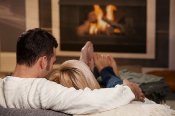 """Young couple hugging on sofa in front of fireplace at home, rear view. Click here for more """"People at Home"""" images:    [url=my_lightbox_contents.php?lightboxID=1507925][img]http://www.nitorphoto.com/istocklightbox/peopleathome.jpg[/img][/url]"""