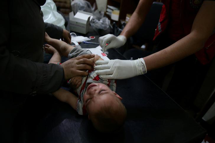 A member of the Syrian Arab Red Crescent administers a vaccination to a child in the rebel held Douma neighborhood of Damascus, Syria May 2, 2016. REUTERS/Bassam Khabieh