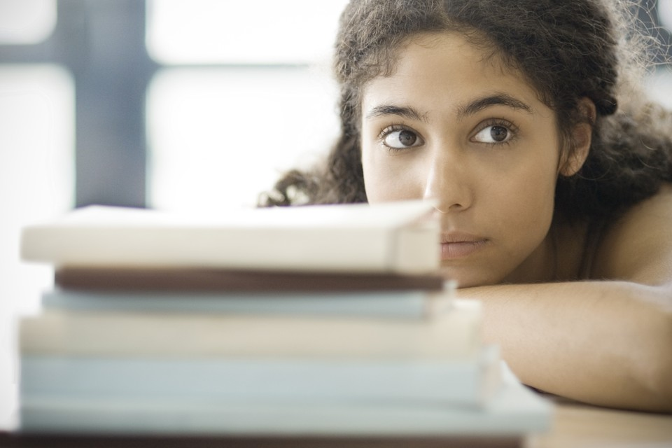 Young Woman Resting Head on Arms, Behind Pile of Books --- Image by © Eric Audras/PhotoAlto/Corbis