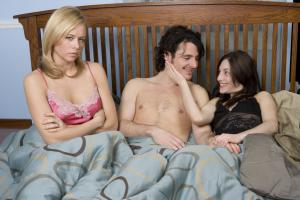 Man in bed with two women, one woman sulking