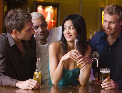 Men talking to woman at bar
