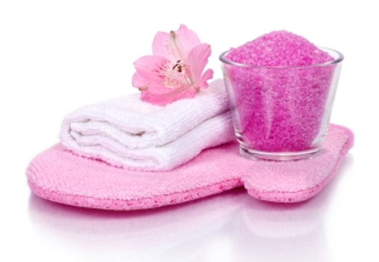 pink bathroom composition with scrubbing glove, bath salt, towel and flower (with reflexion)